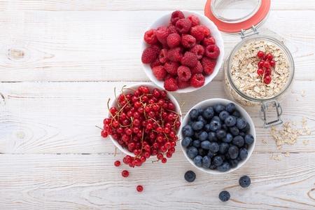 夏の朝食。健康的な朝食 - ベリー、フルーツ、白い木製のテーブル、クローズ アップ トップ ビュー水平にミューズリーの材料。マクロ撮影の選択