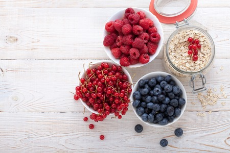 lifestyle: Summer breakfast. Ingredients for healthy breakfast - berries, fruit and muesli on white wooden table, close-up top view horizontal. Macro shot selective focus Stock Photo