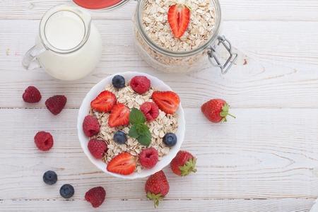 desayuno: Desayuno del verano. Ingredientes para el desayuno saludable - bayas, fruta y muesli en la mesa de madera blanca, primer plano vista superior horizontal. Tiro macro enfoque selectivo