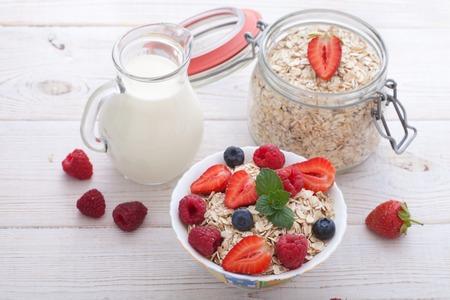 breakfast: Desayuno del verano. Ingredientes para el desayuno saludable - bayas, fruta y muesli en la mesa de madera blanca, primer plano vista superior horizontal. Tiro macro enfoque selectivo