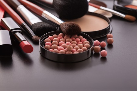Various makeup products on dark background with copyspace Stock Photo