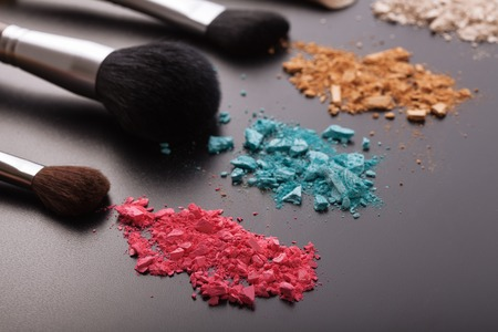 cosmetic products: Makeup brushes on background with colorful powder. Crushed eyeshadow on black background. Abstract background. Selective focus. Stock Photo