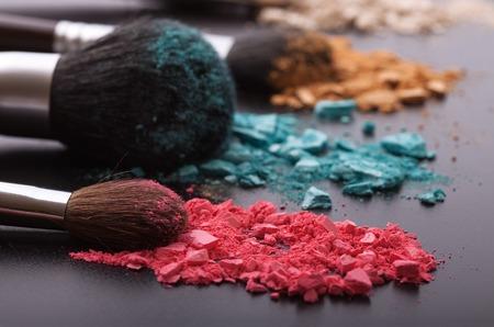productos naturales: Cepillos del maquillaje en el fondo con el polvo colorido. Sombra de ojos machacado en el fondo negro. Resumen de antecedentes. Enfoque selectivo. Foto de archivo