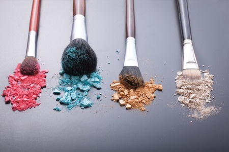 color: Makeup brushes on background with colorful powder. Crushed eyeshadow on black background. Abstract background. Selective focus. Stock Photo