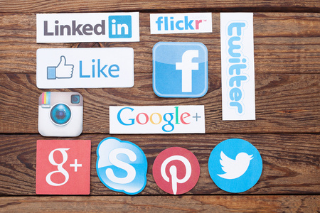 interaccion social: KIEV, Ucrania - 22 de agosto, 2015: Colecci�n de logotipos de medios sociales populares impresos en papel: Facebook, Twitter, Google Plus, Instagram, Pinterest, Skype, YouTube, Linkedin y otros en el fondo de madera