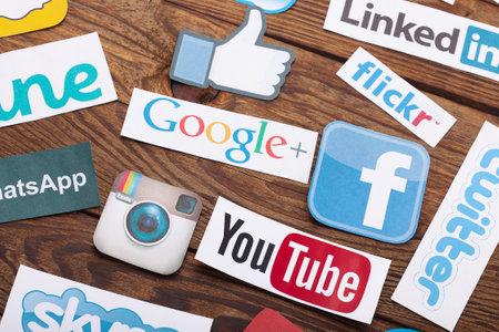 KIEV, Oekraïne - 22 augustus 2015: De inzameling van populaire social media logo's afgedrukt op papier: Facebook, Twitter, Google Plus, Instagram, Pinterest, Skype, YouTube, Linkedin en anderen op houten achtergrond Redactioneel
