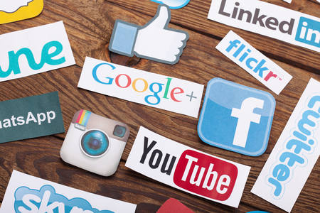 interaccion social: KIEV, Ucrania - 22 de agosto, 2015: Colección de logotipos de medios sociales populares impresos en papel: Facebook, Twitter, Google Plus, Instagram, Pinterest, Skype, YouTube, Linkedin y otros en el fondo de madera