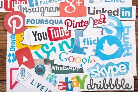 KIEV, UKRAINE - AUGUST 22, 2015:Collection of popular social media logos printed on paper:Facebook, Twitter, Google Plus, Instagram, Pinterest, Skype, YouTube, Linkedin and others on wooden background Éditoriale