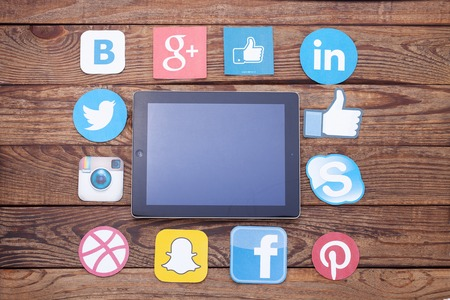 background skype: KIEV, UKRAINE - AUGUST 22, 2015: Famous social media icons such as: Facebook, Twitter, Blogger, Linkedin, Google Plus, Instagram printed on paper and placed around iPad on wooden table background. Editorial