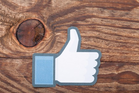 social networking service: KIEV, UKRAINE - AUGUST 22, 2015: Facebook thumbs up sign printed on paper and lies on wooden background. Facebook is well-known social networking service.
