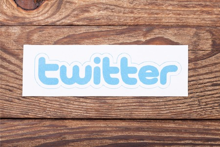 social networking service: KIEV, UKRAINE - AUGUST 22, 2015:Twitter logotype bird printed on paper and lies on wooden background. Twitter is an online social networking service that enables users to send and read short messages.