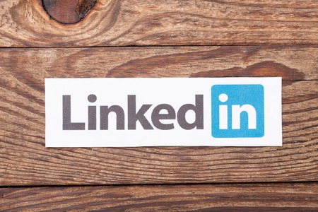 microblog: KIEV, UKRAINE - AUGUST 22, 2015: Linkedin logo sign printed on paper and placed on wooden background. Linkedin is business social networking service.
