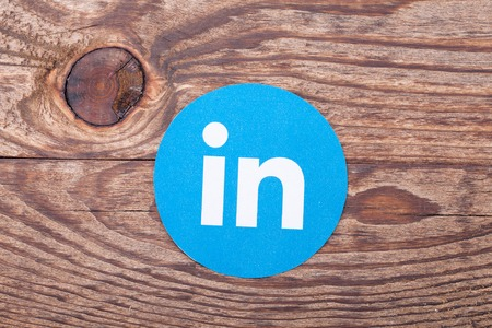 KIEV, UKRAINE - AUGUST 22, 2015: Linkedin logo sign printed on paper and placed on wooden background. Linkedin is business social networking service.