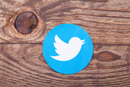 enables: KIEV, UKRAINE - AUGUST 22, 2015:Twitter logotype bird printed on paper and lies on wooden background. Twitter is an online social networking service that enables users to send and read short messages.