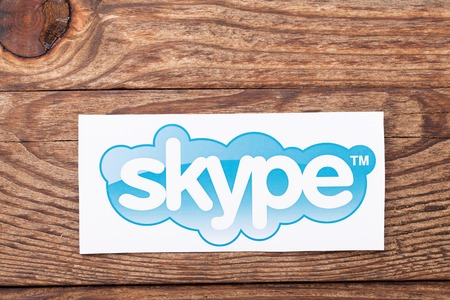background skype: KIEV, UKRAINE - AUGUST 22, 2015: Skype logotype printed on paper and placed on wood background. Skype is a telecommunications application software developed by Microsoft.