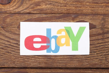 ebay: KIEV, UKRAINE - AUGUST 22, 2015:eBay logotype printed on paper on wooden background. eBay Inc. is an American multinational corporation and e-commerce company, providing sales services via Internet