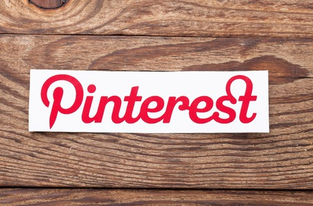 pinterest: KIEV, UKRAINE - AUGUST 22, 2015: Pinterest logotype printed on paper and lies on wooden background. Pinterest is photo sharing website.
