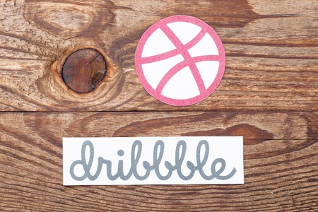 web portal: KIEV, UKRAINE -AUGUST 22, 2015: Dribbble logotype printed on paper. Is global social network for designers. Web portal, the main target audience of which representatives of creative professions.