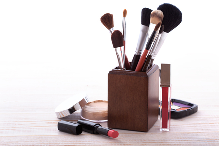 eye shadows: Makeup cosmetics products on white wooden background with copy space. Cosmetics make up artist objects: lipstick, eye shadows, eyeliner, concealer, powder, tools for make-up. Selective focus