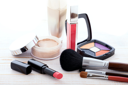 the lipstick: Makeup cosmetics products on white wooden background with copy space. Cosmetics make up artist objects: lipstick, eye shadows, eyeliner, concealer, powder, tools for make-up. Selective focus
