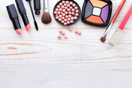 Makeup cosmetics products on white wooden background with copy space. Cosmetics make up artist objects: lipstick, eye shadows, eyeliner, concealer, powder, tools for make-up. Selective focus