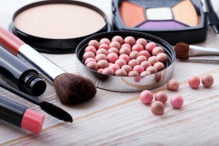 artistas: Productos cosméticos de maquillaje sobre fondo de madera blanco con espacio de copia. Cosméticos componen objetos artista: barra de labios, sombras de ojos, delineador de ojos, corrector, polvo, herramientas para el maquillaje. Enfoque selectivo