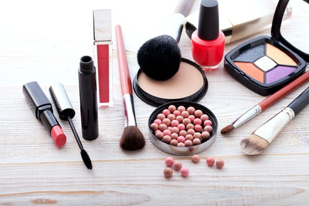 eye shadows: Makeup cosmetics products on white wooden background with copy space. Cosmetics make up artist objects: lipstick, eye shadows, eyeliner, concealer, nail polish, powder, tools for make-up Stock Photo