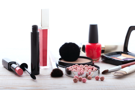 eye shadows: Makeup cosmetics products on white wooden background with copy space. Cosmetics make up artist objects: lipstick, eye shadows, eyeliner, concealer, nail polish, powder, tools for make-up. Selective focus