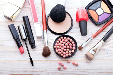l�piz labial: Productos cosm�ticos de maquillaje sobre fondo de madera blanco con espacio de copia. Cosm�ticos componen objetos artista: barra de labios, sombras de ojos, delineador de ojos, corrector, esmalte de u�as, polvos, herramientas para el maquillaje. Enfoque selectivo
