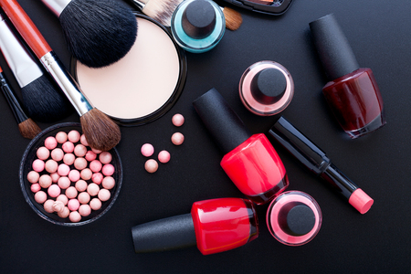 Makeup cosmetics products on dark background with copy space. Cosmetics make up artist objects: lipstick, eye shadows, eyeliner, concealer, nail polish, powder, tools for make-up. Selective focus