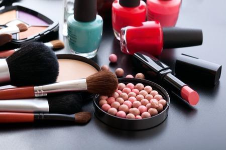 productos de belleza: Productos cosméticos de maquillaje sobre fondo oscuro con espacio de copia. Cosméticos componen objetos artista: barra de labios, sombras de ojos, delineador de ojos, corrector, esmalte de uñas, polvos, herramientas para el maquillaje. Enfoque selectivo