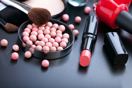 eye shadows: Makeup cosmetics products on dark background with copy space. Cosmetics make up artist objects: lipstick, eye shadows, eyeliner, concealer, nail polish, powder, tools for make-up. Selective focus