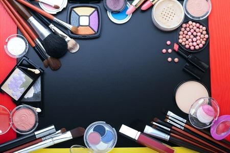 Productos cosméticos de maquillaje sobre fondo oscuro con espacio de copia. Cosméticos componen objetos artista: barra de labios, sombras de ojos, delineador de ojos, corrector, esmalte de uñas, polvos, herramientas para el maquillaje. Enfoque selectivo Foto de archivo - 46697813