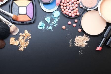 artistas: Productos cosméticos de maquillaje sobre fondo oscuro con espacio de copia. Cosméticos componen objetos artista: barra de labios, sombras de ojos, delineador de ojos, corrector, esmalte de uñas, polvos, herramientas para el maquillaje. Enfoque selectivo