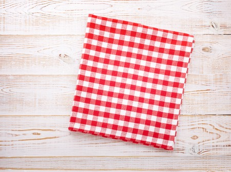 napkin: Wooden kitchen table with empty red tablecloth for dinner. View from above with copy space