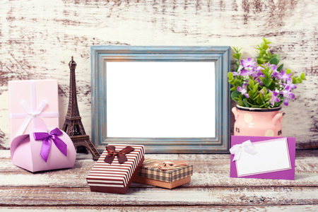 Wooden Frame and romantic accessories with gift boxes on wooden background.