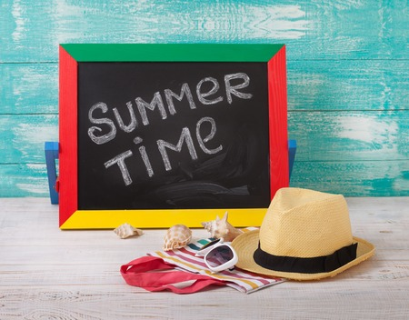 Blackboard with text its summer time. Summer accessories sunglasses, hat, towel on wooden deck