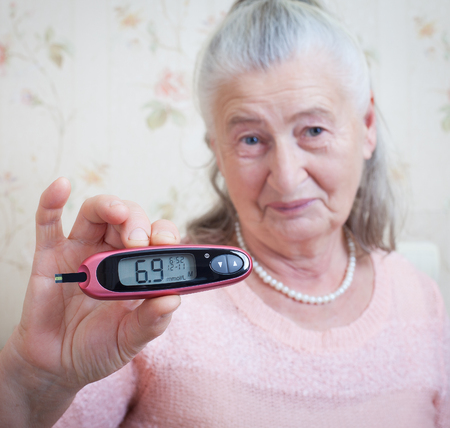 deficient: Medicine, age, diabetes, health care and people concept - senior woman with glucometer checking blood sugar level at home closeup Stock Photo