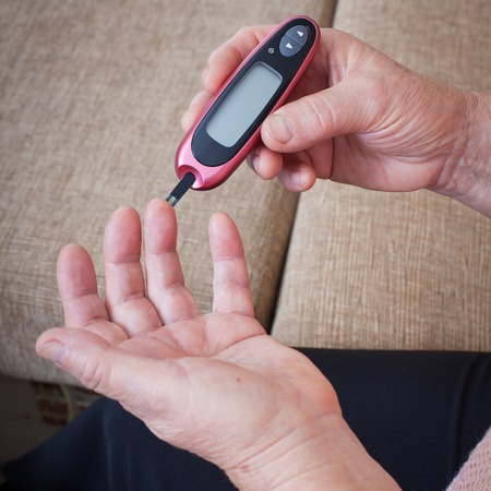 blood glucose level: Woman makes measurement Testing high blood sugar. Diabetes concept glucometer for glucose level blood test in hand Stock Photo
