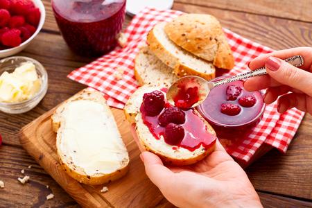 라즈베리 잼을 바르고합니다. 라즈베리 잼 여성 석고 빵과 버터. 트레이에 딸기와 나무 딸기 잼 항아리를 닫습니다