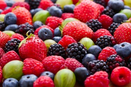 果実背景マクロ、セレクティブ フォーカス。ラズベリーの食欲をそそる、天然ブルーベリー、ジューシーなイチゴ、熟したグーズベリー。明るい背