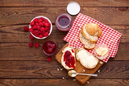 ラズベリー ジャムを中傷します。ラズベリー ジャムのパンとバター。トレイの上の果実とラズベリー ジャムの瓶をクローズ アップ 写真素材