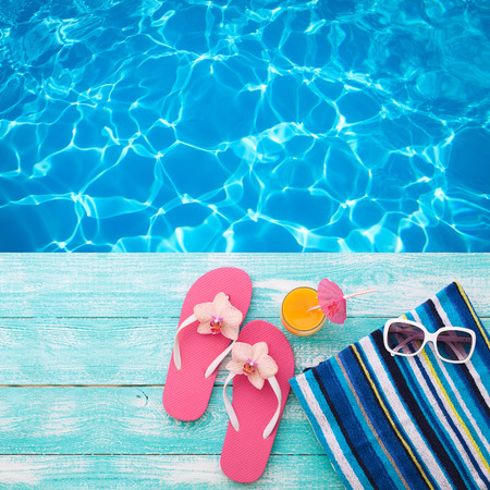 holidays: Summer Holidays in Beach Seashore. Summer drinks. Summer rest. Fashion accessories summer flip flops, hat, sunglasses on bright turquoise board near the pool