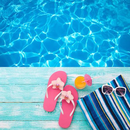 summer: Vacaciones de verano en la playa de la costa. bebidas de verano. Resto del verano. chanclas accesorios de moda del verano, sombrero, gafas de sol a bordo de color turquesa brillante cerca de la piscina