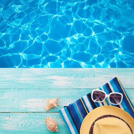 Vacaciones de verano en la playa de la costa. bebidas de verano. Resto del verano. chanclas accesorios de moda del verano, sombrero, gafas de sol a bordo de color turquesa brillante cerca de la piscina Foto de archivo - 54587514