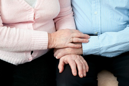 Older Couple Holding Hands close up. Elderly couple with beautiful hands posing together in  close embrace Stock Photo