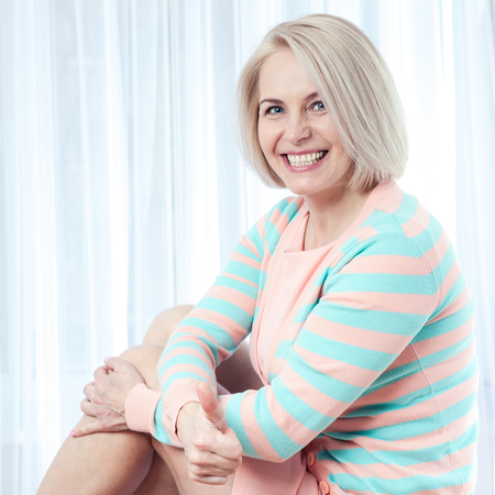 Active beautiful middle-aged woman smiling amiably, showing thumbs up and looking at camera.