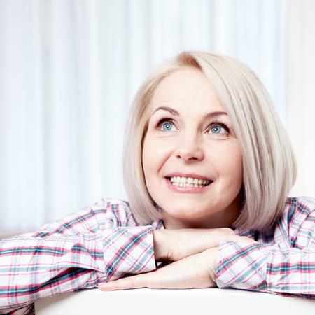 Aktive schöne Frau mittleren Alters, freundlich lächelnd und zu Hause im Wohnzimmer nach oben. Gesicht der Frau Nahaufnahme