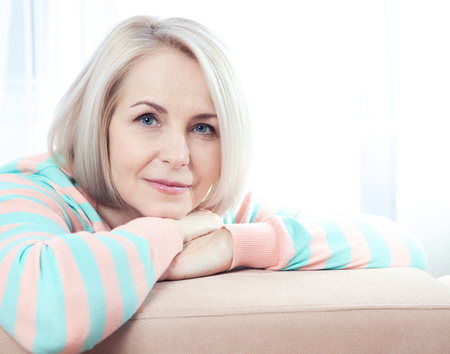 Active beautiful middle aged woman smiling friendly and looking into the camera at home. Woman's face close up. Stock Photo