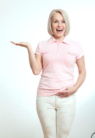 흰색 배경에 고립 된 copyspace 가리키는 친절 한 웃는 중간 나이 든된 여자 스톡 콘텐츠